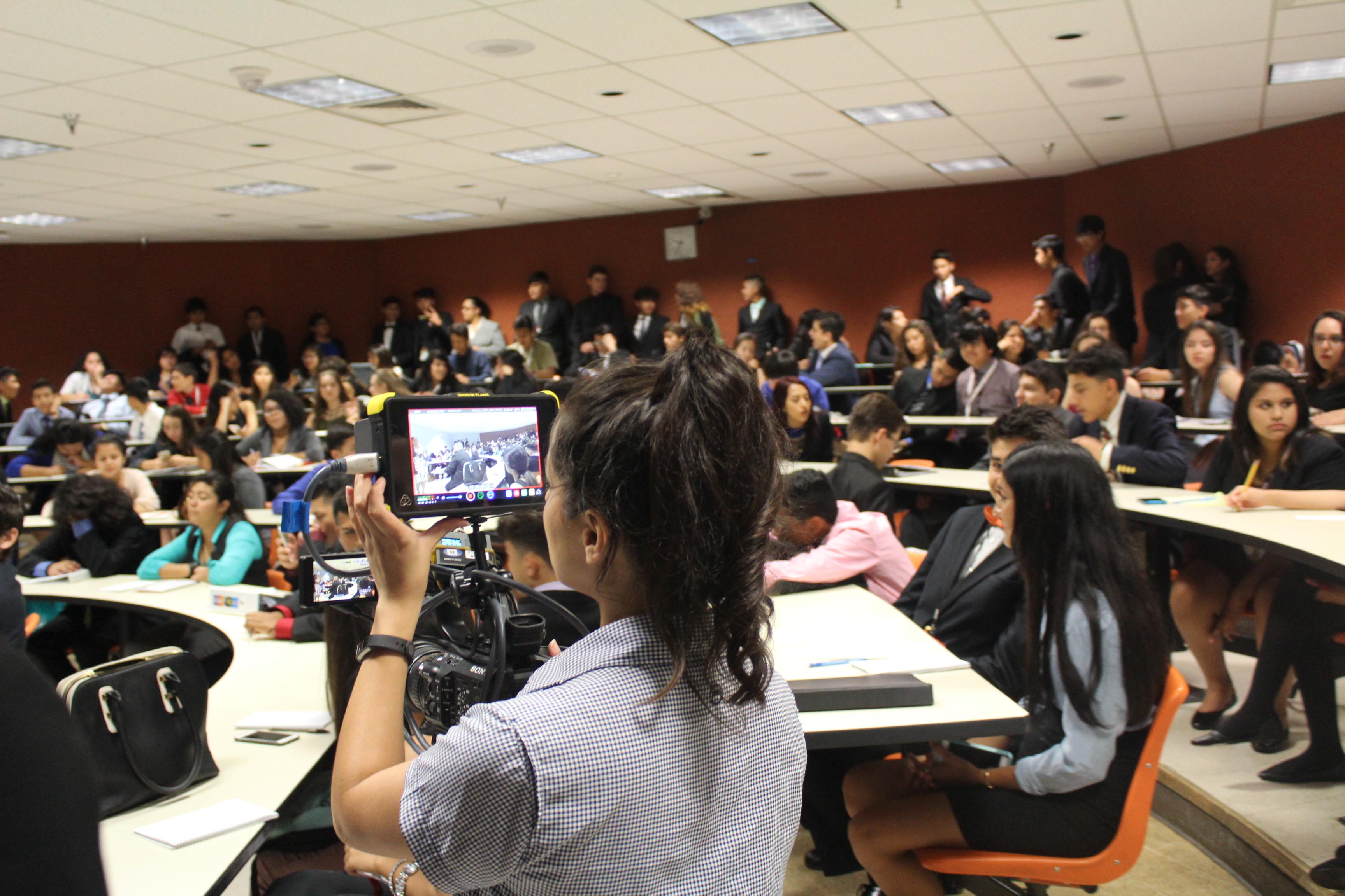 A member of the DishLATINO crew films students at the 2016 Texas Ambassador Great Debate
