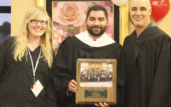 Zachary Gonzalez, NHI director of Collegiate Affairs, presents a gift to two Saint Leo University representatives: Nicole Lesko, Associate Director of Events and Campus Visits, and John LaRosa, Assistant Vice President, Campus Enrollment