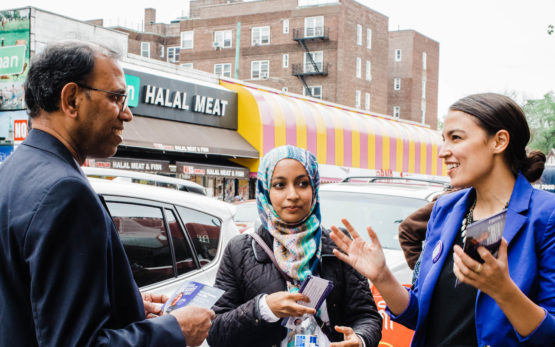 Alexandria Ocasio-Cortez, campaigning in New York City, talking to a man and a woman